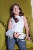 Kleines nahöstliches Mädchen, das krankes schlechtes glaubt und digitales Blutdruckgerät hält Stockfoto