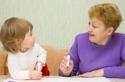Kleines nettes Anstrichmädchen mit Großmutter Lizenzfreies Stockbild