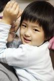 Kleines nettes asiatisches Mädchenlächeln Stockfotos