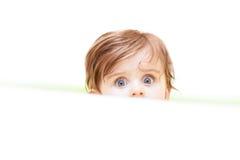 Kleines nettes Baby, das aus dem Bad heraus späht stockfoto