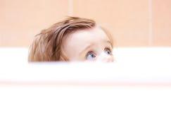Kleines nettes Baby, das aus dem Bad heraus späht stockfotografie
