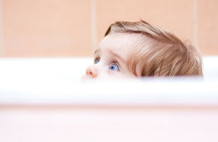 Kleines nettes Baby, das aus dem Bad heraus späht Stockbild
