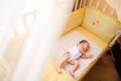 Kleines nettes Baby, das in der Krippe schläft stockfoto