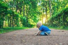 Kleines nettes Baby mit Nippel sitzt auf dem Fußweg im traumhaften Wald ganz allein Kleiner Junge, der aus den Grund sitzt Lizenzfreie Stockbilder