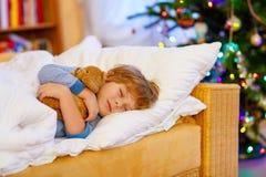 Kleines nettes blondes Kind, das unter Weihnachtsbaum schläft Lizenzfreies Stockbild