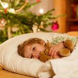 Kleines nettes blondes Kind, das unter Weihnachtsbaum schläft Lizenzfreie Stockfotos