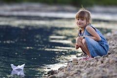 Kleines nettes blondes langhaariges Mädchen im blauen Kleid auf Riverbank peb Lizenzfreie Stockfotografie