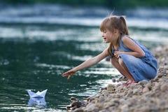 Kleines nettes blondes langhaariges Mädchen im blauen Kleid auf Riverbank peb Stockfotografie