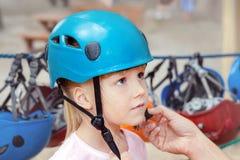 Kleines nettes blondes Mädchen, das auf Sturzhelm sich setzt Bringen Sie helfende Tochter hervor, um Sturzhelm vor extremer Sport stockfotos