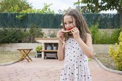 Kleines nettes blondes Mädchen, das Wassermelone isst Stockfoto