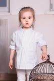 Kleines nettes blondes Mädchen in gestreiftem Hemd steht und verlängert Hand Lizenzfreie Stockbilder