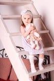 Kleines nettes blondes Mädchen im Kleid, das auf hölzerner Treppe mit so sitzt Stockbild