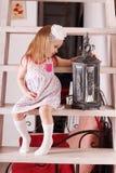 Kleines nettes blondes Mädchen im Kleid, das auf Treppe mit wi sitzt Stockfotos