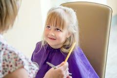 Kleines nettes blondes Mädchen lächelt und betrachtet Friseur während des Haarschnittprozesses Friseur hält Kamm und Scheren in e Lizenzfreie Stockfotos