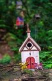 Kleines nettes buntes selbst gemachtes feenhaftes Haus, das auf LOGON-Waldwald sitzt lizenzfreie stockbilder