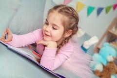 Kleines nettes Feierkonzept des Mädchens zu Hause auf dem Sofazeichnen froh stockfotos