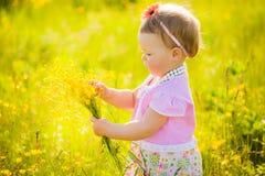 Kleines nettes Kind, das allein im Frühjahr spielen oder sonnige Wiese des Sommers Stockfoto