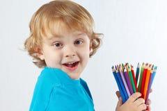 Kleines nettes Kind hält Farbbleistifte an Lizenzfreie Stockfotos