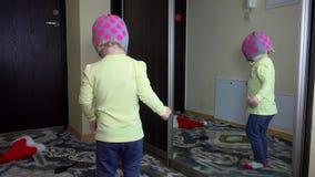 Kleines nettes Kindermädchen lächeln vor Spiegel zu Hause geziert stock footage