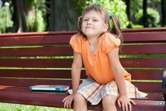 Kleines nettes lächelndes Mädchen mit Buch auf Bank Stockbild