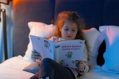 Kleines nettes langhaariges Mädchen in einer Strickjacke, die interessiert schaut lizenzfreies stockfoto