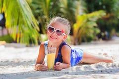 Kleines nettes Mädchen auf dem Sand am Strand in den Sonnenbrillen mit einem Glas exotischem Cocktailsaft Lizenzfreies Stockfoto