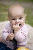 Kleines nettes Mädchen, das auf Gras im Park sitzt. stockbild