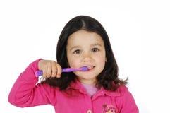 Kleines nettes Mädchen, das die Zähne putzt stockfotos