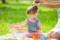 Kleines nettes Mädchen, das an einem Picknick spielt stockbild