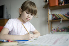 Kleines nettes Mädchen, das Heimarbeit tut. Lizenzfreie Stockbilder
