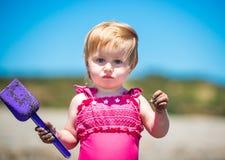 Kleines nettes Mädchen, das im Sand spielt Stockbilder