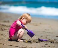 Kleines nettes Mädchen, das im Sand spielt Lizenzfreie Stockbilder