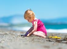 Kleines nettes Mädchen, das im Sand spielt Lizenzfreies Stockbild