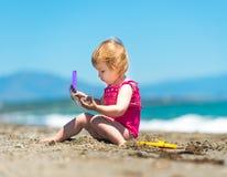 Kleines nettes Mädchen, das im Sand spielt Stockfoto