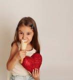 Kleines nettes Mädchen, das Spaß mit süßem sahnigem Hauch und rotem Herzen hat Lizenzfreies Stockbild