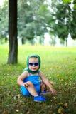 Kleines nettes Mädchen in der blauen Klage mit grünem Halstuch und SU Lizenzfreies Stockfoto