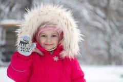 Kleines nettes Mädchen in einer großen Pelzhaube, die ihre Hand wellenartig bewegt Stockfotografie