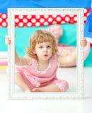Kleines nettes Mädchen in einer rosa Klage, die auf dem Boden sitzt und über hölzernem weißem Rahmen lächelt Lizenzfreie Stockbilder