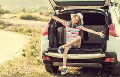 Kleines nettes Mädchen im Stamm eines Autos mit Koffern lizenzfreie stockfotografie