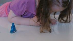 Kleines nettes Mädchen malt ihre Nägel mit blauem Lack stock video
