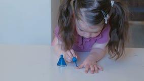 Kleines nettes Mädchen malt ihre Nägel mit blauem Lack stock video footage