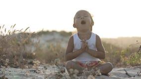 Kleines nettes Mädchen meditiert im Freien bei Sonnenuntergang mit schönem natürlichem Licht stock video footage