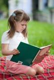Kleines nettes Mädchen mit Buch auf Plaid im Park Lizenzfreie Stockfotografie