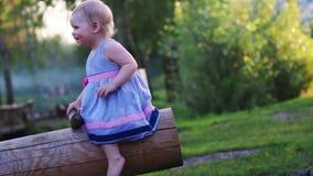 Kleines nettes Mädchen mit dem blonden Haar auf Schwingen stock footage