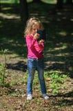 Kleines nettes Mädchen mit dem blonden Haar verwendet blaues Smartphone, das im Park steht Weibliches Kind, das Foto durch Mobile lizenzfreie stockfotografie