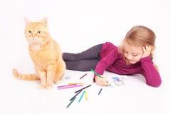 Kleines nettes Mädchen mit farbigen Bleistiften und roten der Katze, die auf dem Boden liegt Stockfotografie
