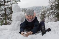 Kleines nettes Mädchen sculpts Schneemann spiel Lizenzfreie Stockbilder