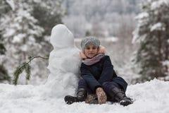 Kleines nettes Mädchen sculpts Schneemann Winter Stockbilder