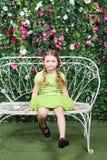 Kleines nettes Mädchen sitzt auf Bank Stockbilder