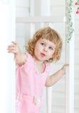 Kleines nettes Mädchen untersucht die Straße und das Lächeln von hinten Tür Lizenzfreies Stockbild